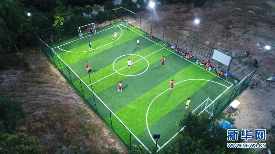 6月19日,足球爱好者在河南省焦作市武陟县一处绿茵场进行比赛。夜幕降临,热浪散去,足球爱好者在绿茵场上展开较量,在夏日夜晚感受足球运动带来的快乐。新华社发 冯小敏 摄