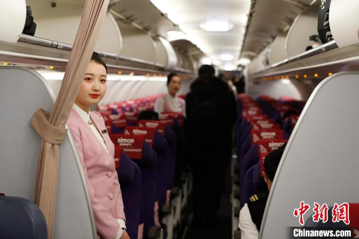 王姝樱在客舱里迎接旅客的到来。 殷立勤 摄